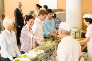 Business colleagues in cafeteria cook serve fresh healthy food m