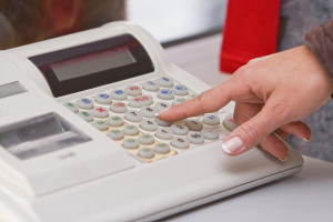 woman pressing button on electronic cash register